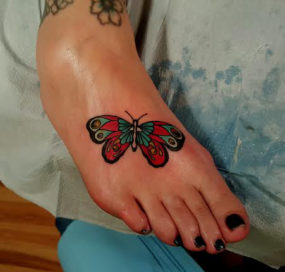 Butterfly on foot tattooed by Chad