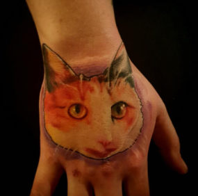 Cat portrait on hand tattooed by Chad