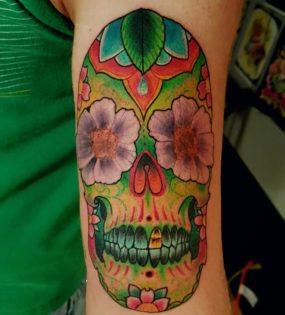 Colorful sugar skull tattooed by Chad
