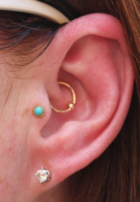 Daith Piercing with gold ring and Tragus with 14k gold and Turquoise stud done at Laughing Buddha Tattoo & Body Piercing Seattle, WA Capitol Hill